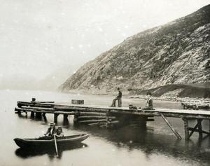 Ved den gamle trekaien på Vadla i Jøsenfjorden. Jentene i pråmen kan vera Olive og Esther Archer. Gutane på bryggja er truleg Harold (til venstre) og Norman Archer. Vi ser utover på nordsida av fjorden.