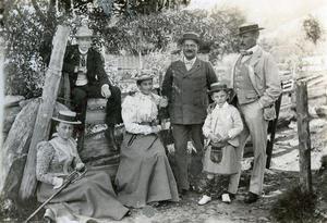 Archerfamilie og vener på tur på Vasshus. Det er truleg Harold Archer som sit på grinda til venstre, og så er det Alice og Walter Archer i midten. Vi kjenner ikkje namna på kvinna til venstre og mannen og guten til høgre.