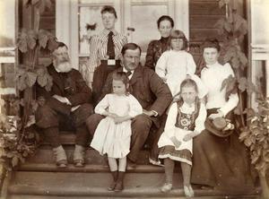 """Gruppebilde med gjester på trappa ein gong tidleg i 1890-åra. Walter Archer i midten med dottera Esther i fanget. Alice har dottera Ruth framfor seg. Den tredje dottera, Olive, sit framme til høgre i hardangerdrakt. Dama heilt til høgre kan vera barnepassaren, the nurse, eller """"nørså"""" som folk på Sand sa. Mannen til venstre med gamasjer er truleg ein engelsk gjest."""