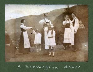 """Det er hageselskap på Rophaug i 1913. Tenestejentene dansar """"a Norwegian dance"""" og har med seg eit par småjenter i kvite kjolar. Tenestejentene var frå lokalsamfunnet, småjentene ser ut til å vera av fint folk, kanskje engelske gjester."""