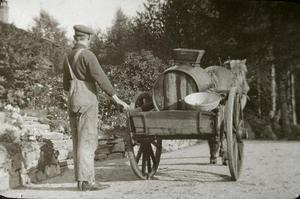 Det var mange tenestefolk hos dei engelske, og ikkje berre kvinner. Her er Ola Brommeland (1889-1970) frå Sand ute og køyrer vatn ein sommardag i 1912-1913. Truleg er det vatning i hagen han driv med. Han arbeidde lenge for Archer'ane, m.a. som gartnar. Foto: Miss Law.