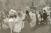 Jenter i barneselskap på Rophaug i 1912-1913. Dei er sessa til bords og får fint brød og bollar og saft i fine koppar. Foto: Miss Law.