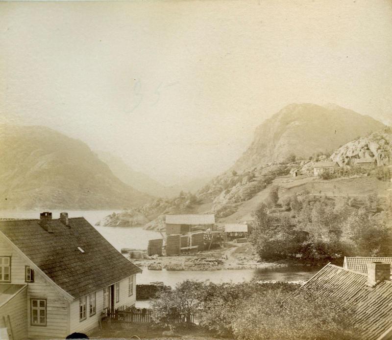 Hålandsosen i Erfjord i 1888. Krambua til venstre dreiv Lars Torjussen Våge frå 1870. I midten på andre sida av elva ser vi Hålandssaga med høge bordstablar på utsida.