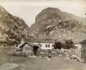 """Gardstuna i Føre ligg halvannan kilometer inn gjennom dalen frå fjorden. Her er dei fotograferte i 1888 med den dominerande fjellformasjonen Odden bakanfor. """"Farm house at Forre 1888"""" har Alice Archer skrive under bildet."""