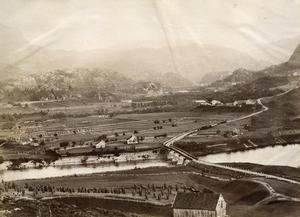 Utsyn frå Rophaug mot Gardaneset og Sandsbygda. I framgrunnen ser vi kornåkrar og marker på Brakahaugen under Lagarhus. Tjelmane ligg til venstre for brua på andre sida av Lågen. Gardshusa på Haua ligg ved vegen oppover til høgre og Helland i bakgrunnen til venstre. Bildet kan vera frå kring 1895. Det er haust, kornåkrane er skorne og kornbanda står på staur.