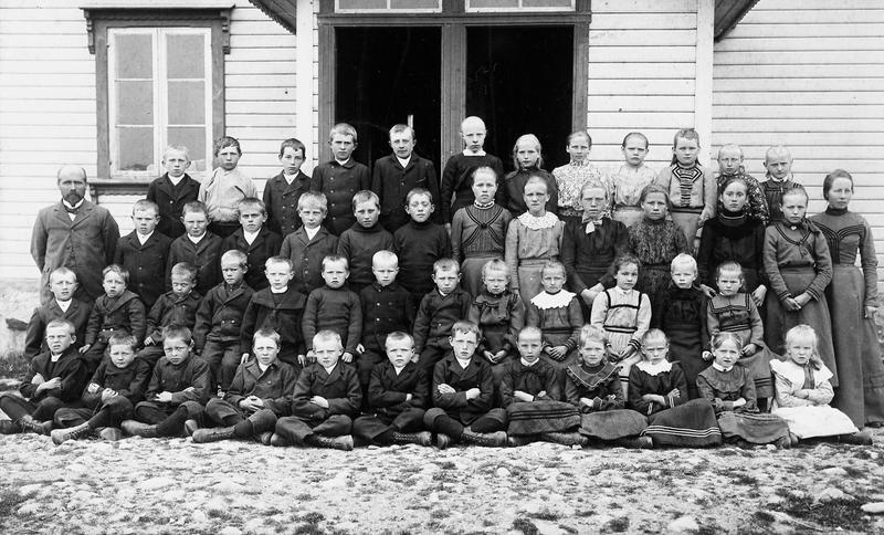 I åra mellom 1903 og 1906 fotograferte P. P. Herdenberg frå Kristiania skuleklassar på Jæren og i Ryfylke. Her har han fotografert både små- og storskulen ved ein av skulane i Randaberg kring 1905. Det er ikkje kjent om skulefotografring var einaste oppdraget hans i Rogaland. Herdenberg brukte ein påkosta kartong-type med fine pynteborder, same kartongtypen som Rasmus P. Thu nytta til skulebiletet han tok heime på Tu i Klepp i 1897 (sjå fig. 5). Foto: P. P. Herdenberg, Kristiania.