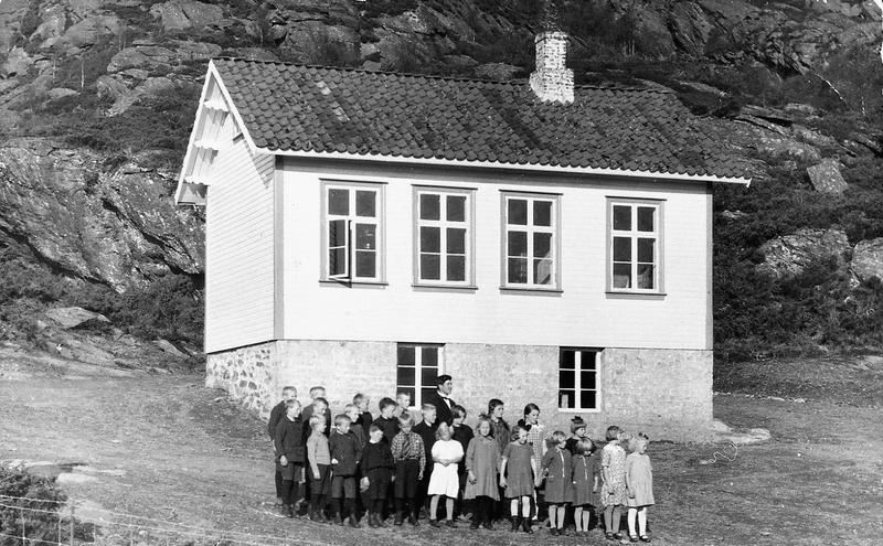 Lærar Odd Roalkvam med elevflokken sin framfor Neset skule i Nedstrand (Tysvær kommune), skuleåret 1930-1931. Kanskje var det ein lokal bygdefotograf som tok biletet. I ettertid er det ikkje alltid lett å identifisera fotografen når vi bare har ein kopi for hand, og ikkje originalpositiven. Fotopapirtypen og fotokartongtypen kan nemleg i mange tilfelle gje ein peikepinn på kven fotografen var. Foto: Ukjend.