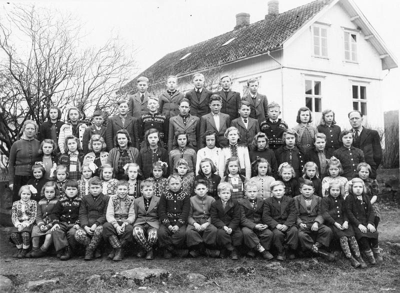 Elevane ved Bjerkreim skule i 1946 med lærarane Hanna Mykjedal (t.v.) og Klaus Bjerkreim (t.h.). Om vi kunne samanlikna dette biletet med tilsvarande skulebilete frå 1946 frå alle kommunane i fylket, ville vi sjå at klesskikkane var ulike frå distrikt til distrikt, og mellom by og land. I dag kler skulebarna seg likt i heile fylket. Elevane i Bjerkreim merka seg truleg ut i 1946 når det galdt bruk av selbusokkar. Foto: Ukjend, truleg J. W. Eskildsen, Egersund eller Carl J. Olsen, Stavanger.