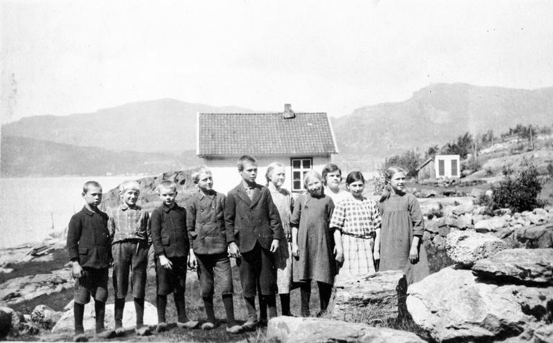 I 1925 fotograferte lærar Oluf Bjelland elevane ved Finnvik skule i Imsland (Vindafjord kommune). Biletet viser også miljøet rundt skulehuset og det vesle uthuset i bakgrunnen. Oluf Bjelland må ha vore ein dyktig amatørfotograf med godt kamera. Dette fotografiet har like god teknisk kvalitet og like god komposisjon som bileta dei profesjonelle fotografane tok når dei stilte barna opp på strame rekkjer. Foto: Oluf Bjelland.