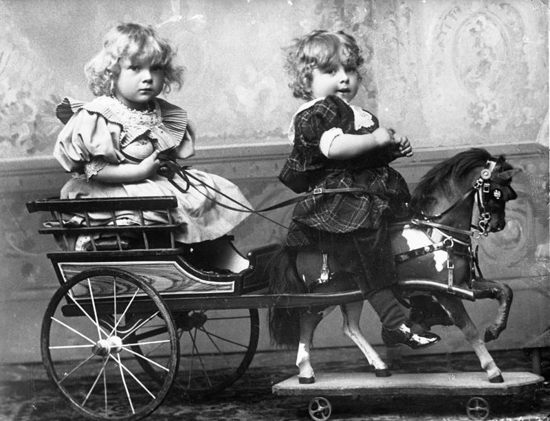 To ukjende småbarn i atelieret til Henrichsen & Co. Også dette fotografiet er frå dei første åra etter at firmaet etablerte seg i Stavanger i 1901. Etter 1900 annonserte fotografane i Stavanger for første gong at dei leverte portrett av små og større barn.  Dei fleste ateliera i byen vart utstyrte med leiker. Den flotte hesten med vogn hos Henrichsen & Co var likevel uvanleg. Foto: Henrichsen & Co. Glasnegativ. Privatarkiv nr. 430, Hakon Johannessen, Statsarkivet i Stavanger.