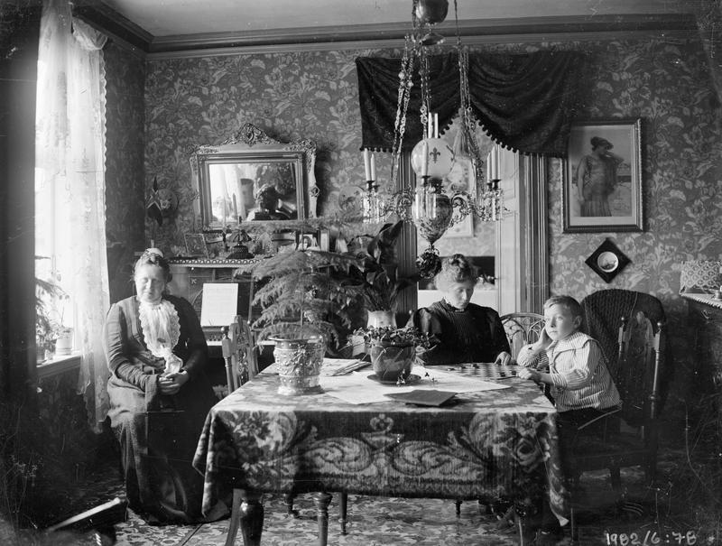 """Negativarkivet etter firmaet Henrichsen & Co inneheld mange oppdragsfotografi frå """"bedrestilte"""" heimar i byen. Mange av desse interiørfotografia er ukjende for oss i dag.Dette er eitt av dei. Me skulle kanskje tru det var kvinnelege fotografar som tok bilete av medsøstre i heimane deira, som i dette tilfellet. Dette fotografiet kan også  vera frå tida etter at Karen Henrichsen og Hakon Johannessen skilde lag i 1907.Henrichsen fann seg då eit nytt atelier i byen medan Johannessen overtok firmaet og negativarkivet i Kongsgata 28.       Foto: Henrichsen & Co eller Hakon Johannessen. Glasnegativ. Privatarkiv nr. 430, Hakon Johannessen, Statsarkivet i Stavanger."""