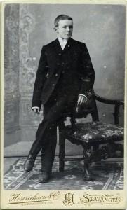 Dei første åra etter 1900 annonserte fleire fotografar i Stavanger at dei tok konfirmantbilete. Her er ein ukjend gut hos Henrichsen & Co, ikkje lenge etter 1901. Dette er den første, kjende kartongtypen til firmaet. Foto: Henrichsen & Co. Privat fotosamling. Statsarkivet i Stavanger.