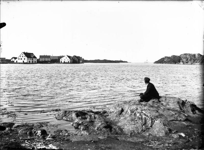 En mann sitter med ryggen til fotografen og skuer utover mot Vibrandsøy, vest for Haugesund. Fotograf: Thea Larsen, MHB-F.003007, Karmsund folkemuseums fotosamling.