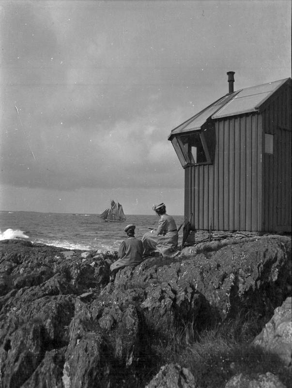 Kvinnene sitter med ryggen til fotografen og ser ut på havet og seilskuten som passerer. Stedet er Kvalen, like nord for Haugesund, og de sitter like ved den gamle fyrlykten. Det er ingen tvil om fotografens komposisjon, med kvinnene og seilskuten som sentrale element i bildet. Fotograf: Thea Larsen, MHB-F.003021, Karmsund folkemuseums fotosamling.