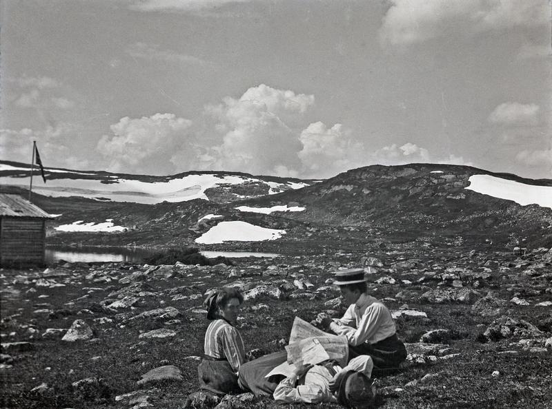 Tre damer på tur i høyfjellet. Sannsynligvis er motivet fra et fjellparti i nærheten av Røldal eller Haukeli. Damene slapper av i lyngen, og en av dem ser også ut til å ha sovnet, med avisen liggende over seg.Fotograf: Thea Larsen, MHB-F.007809, Karmsund folkemuseums fotosamling.