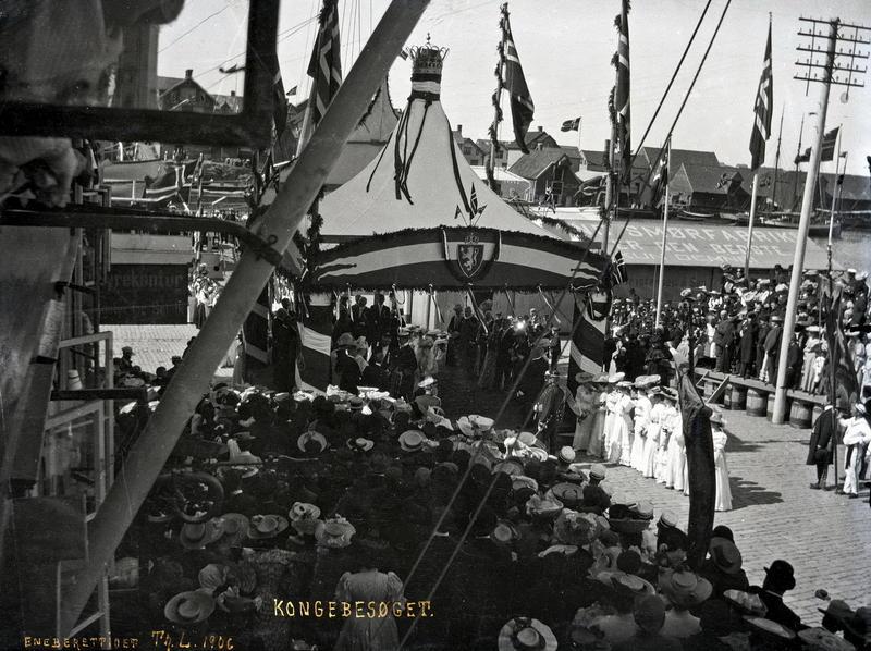 Under kongebesøket i 1906 var Thea Larsen i Torggaten og fotograferte da kongeskipet la til. Kan hun ha stått i kjøpmann Peder Amlies hus i Torggt. 3? Dette er et eksempel på et motiv som ble trykket som postkort. På glassplaten er det skrevet «Kongebesøget.»t «Eneberettiget Th. L. 1906». Fotograf: Thea Larsen MHB-F.007862, Karmsund folkemuseums fotosamling.