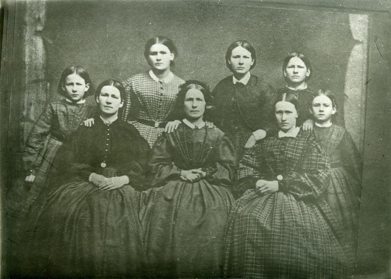 Fru Cecilie Asbjørnsdatter Larsen Kro, med sine døtre. Sittende foran fra venstre: Anna (1840 – 1914), g.m. Peder Amlie i Haugesund. Cecilie Larsen (1812 – 1881). Marie (1838-1950), g.m. Arenth Anda. Stående bak fra venstre: Cecilie, Karen, Thea, Laura (1855-1877) g.m. Arne Lothe i Haugesund og Alida. The Larsen bor sannsynligvis ennå hjemme på denne tiden, og fotografiet må ha vært tatt før hun konfirmerte seg i 1862. Ukjent fotograf, MHB-F.010409,Karmsund folkemuseums fotosamling.