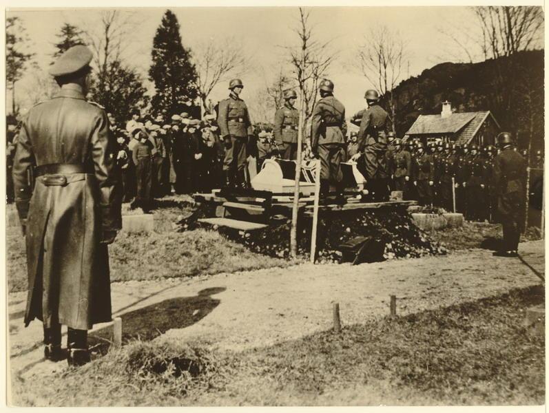 Egersund kirkegård, Årstad 17 april 1940. Begravelse av tysk flyger som hadde forulykket. Kisten settes på grava. Ortskomandant Rittmeister Friedrich R. Eickhorn i giv akt. Vi ser at en rekke sivile nordmenn var også møtte fram til gravferden.