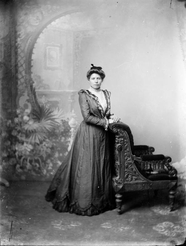 Atelierfotografi av ukjent dame. Stolen i bildet er en av fotoatelierets ofte brukte rekvisitter. Bakgrunnen er den samme som er brukt i DFF-EHT1125 (ovenfor, av skoleklassen). Cirka 1890-1910. Foto: E. H. Torjusen, DFF-EHT0095.