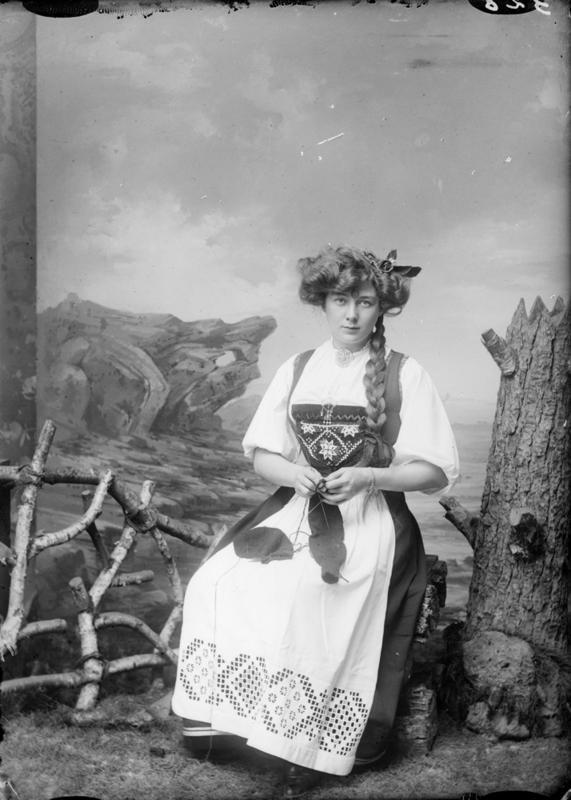 Atelierfotografi av Borghild Hammer. Hun sitter og strikker med bunad på. Rekvisitter som skal gi inntrykk av å være på fjellet. Cirka 1890-1910. Foto: E. H. Torjusen, DFF-EHT0521.