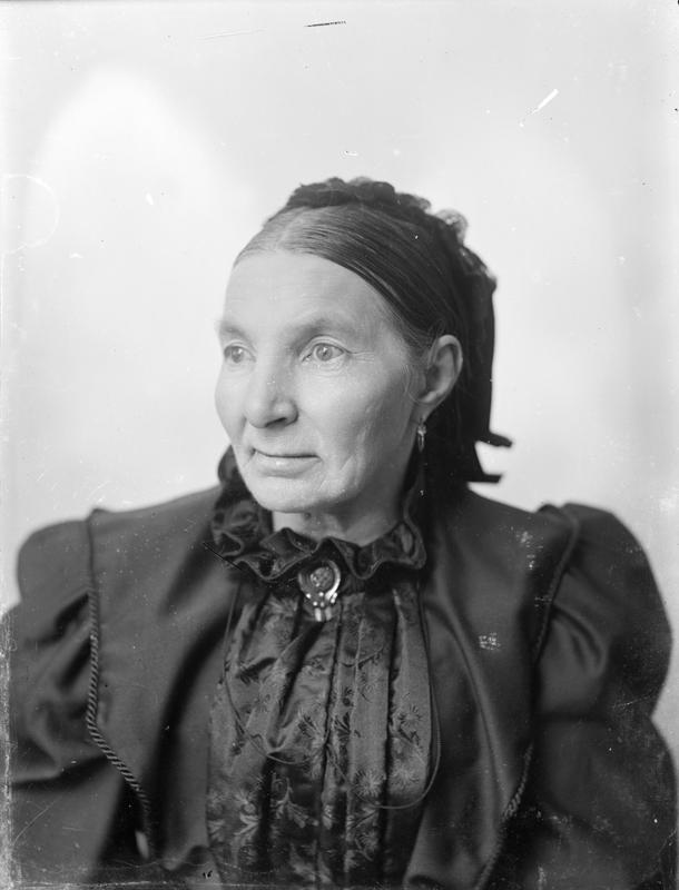 Atelierfotografi av ukjent dame, nærbilde. Fokus er skarp i ansikt og bryst, med økende grad av dybdeuskarphet lenger bakover. Cirka 1890-1910. Foto: E. H. Torjusen, DFF-EHT1065.