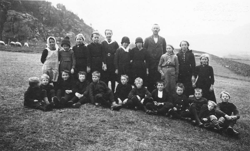 I 1920- og 1930-åra var reisesekreær J. Sørå frå Rørvik fleire gonger i Rogaland. Han fotograferte både skuleklassar og barnelosjar. Barna vart stilte opp ute slik som på dette fotografiet frå Førland skule i Suldal hausten 1921. Lærar Kornelius Risa står saman med barna i skulekrinsen. Det spesielle med Sørå sine fotografi er at han leverte dei på postkortkartongar. Foto: J. Sørå, Rørvik.