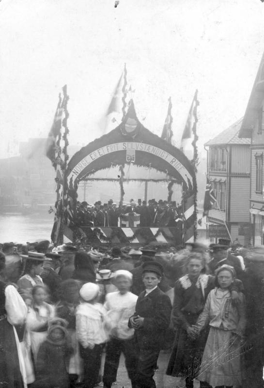 """Kristofa er en av svært mange fotografer som har foreviget høytidelighetene i 1905. Her er barn og voksne samlet i Torgbakken 17. mai 1905. Tribunen er pyntet og dekorert med norske flagg og ordene """"Norge er et frit, selvstændig rige"""". Firmanavnet i 1905 er Kristofa Jansen Grøn. Arkivreferanse: MHB-F.000336."""
