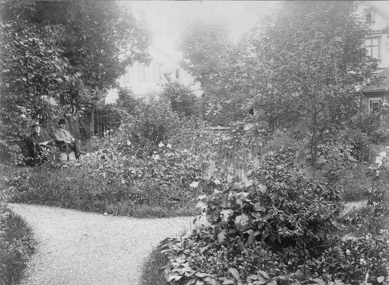 Kristofa Jansen har også fotografert utenfor atelieret. Her er kemner T. Manger og sønnen Thomas Manger fotografert sittende i hagen på eiendommen sin i Haraldsgt. 131. I bakgrunnen ser vi Sørhauggt. 133. Firmanavnet er Kristofa Jansen Grøn og fotografiet kan derfor dateres til etter 1901. Arkivreferanse: MHB-F.002368.