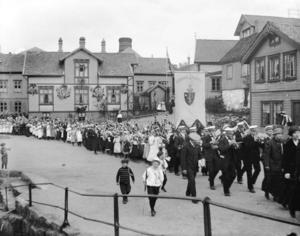 Barnetoget 17. mai 1914 passerer planen ved Fajansefabrikken på Damsgård. Huset i bakgrunnen har ekstra fin lomsterutsmykning. Det spørs om ikke 100-års markeringen for Grunnloven på Eidsvold 1814 gjorde denne 17. mai-markeringen ekstra høytidelig.