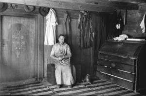 Et fint og innholdsrikt hverdagsbilde fra 1915, trolig fra Berge i Helleland. Dette fotografiet er sjeldent. Det finnes nemlig få tilsvarende interiørbilder fra vanlige hjem i Dalane. Er det noen som kjenner motivet og som kan hjelpe oss med opplysninger?