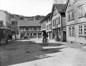 Her er en syklist i Johan Feyers gate på vei mot torvet med mange parkerte hestekjøretøyer. Året er 1914.
