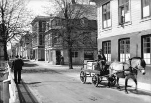 Her er vi i Strandgaten. Baker Haakon Hellvig bringer ut varer med hest og vogn og passerer Middelskolen. Fotografiet er fra ca. 1935.