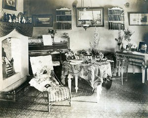 Interiørbilde frå stova på Rophaug med peis, piano og korgmøblar.