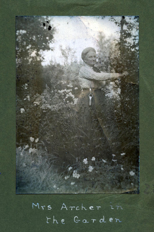 Alice Archer var ikkje berre interessert i fotografering. Ho hadde også stor interesse for hagearbeid, og den fine hagen på Rophaug var det ho som stod for, sjølv om ho hadde tenarhjelp til å få gjort arbeidet. Den snaue tomta klarte ho å kle med mange slags tre og blomar. Det blomstra frå tidleg om våren til seint på hausten. Her er ho i arbeid i hagen ein sommardag i 1913.