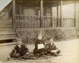 Dei same tre Archerborna (Edward, Olive og Harold) er plasserte på pledd på grusgangen utfor huset i august 1887.