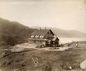 Dette bildet frå Rophaug er truleg frå sommaren 1888. Anleggsarbeidet på uteområdet er enno ikkje ferdig. Legg merke til tønnene i brystet på huset for samling av regnvatn frå taket.