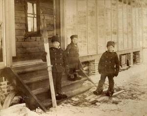 Det er vinter og litt snø, og dei tre eldste borna Edward, Olive og Harold i Archerfamilien er ute. Gutane prøver seg på ski, Olive er enno tilskodar. Bildet er truleg frå 1887.