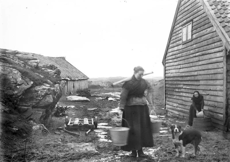 Fra Håland på Kvitsøy. Huset til høyre tilhørte Hans H. Haaland, gården Lauritz Haaland kom fra. Løa til venstre tilhørte Kristian eller hans far Ole Haaland. I dag tilhører den Peder E. Haaland. To ukjente kvinner på fotografiet, trolig ukjente gårdsfolk. Den ene bærer to vannbøtter i et åk. Foto: Stavanger Sjøfartsmuseum, ST.S 1983-057-0101