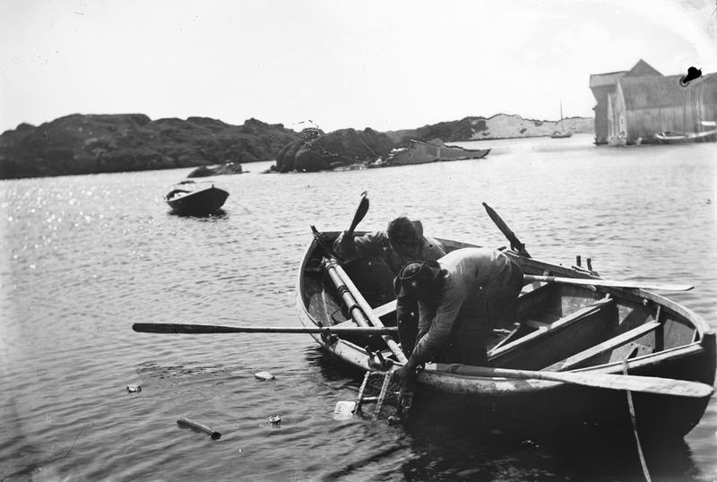To menn driver hummerfiske fra robåt. Bildet er tatt ved Ydstebøhavn på Kvitsøy, sett mot sør. Midt i bildet ligger Skjåskjær, Rossøy ligger til venstre og Grønningen ligger bak til høyre. Helt til høyre ligger fyrvesenets sjøhus med kvist. Foto: Stavanger Sjøfartsmuseum, ST.S 1983-057-0153.