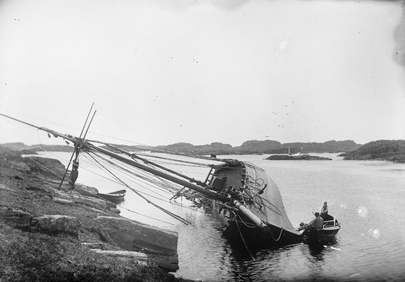To menn i robåt kjølhaler et seilskip. Fotografiet er tatt ved Haganes, sett mot øst. Foto: Stavanger Sjøfartsmuseum, ST.S 1983-057-0157.