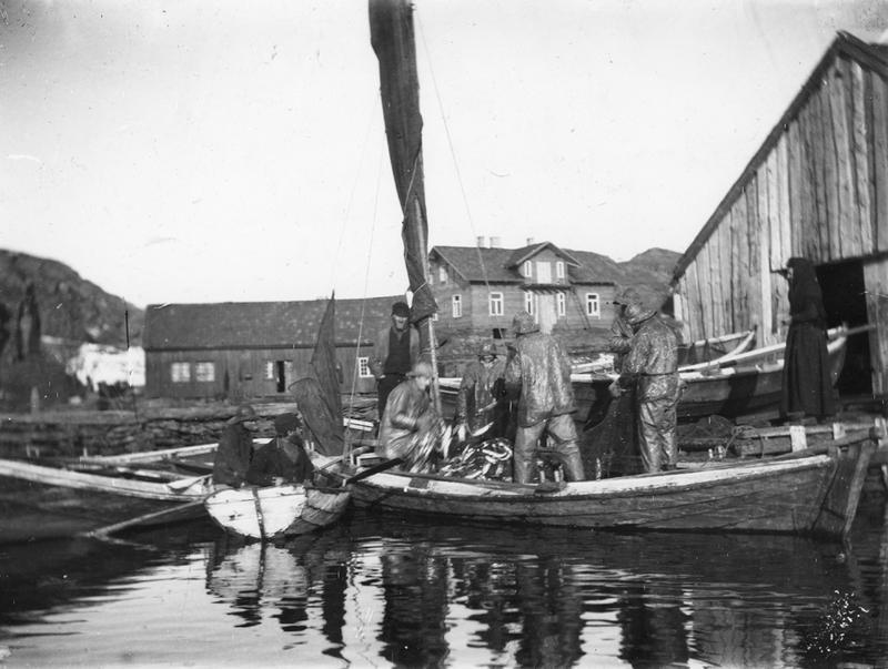 Motivet viser fiskere som har kommet inn til Ydstebøhavn med sild. Lauritz Haalands villa ligger midt i bildet til høyre, det er under bygning. Bildet er tatt ca 1885. Foto: Stavanger Sjøfartsmuseum, ST.S 1983-057-0191.