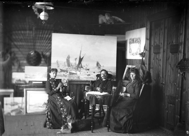 Interiør fra et kunstatelier. Lauritz Haalands malerier står på et staffeli i bakgrunnen. De avfotograferte er mest trolig Lauritz Haaland med familie. Foto: Stavanger Sjøfartsmuseum, ST.S 1983-057-204.