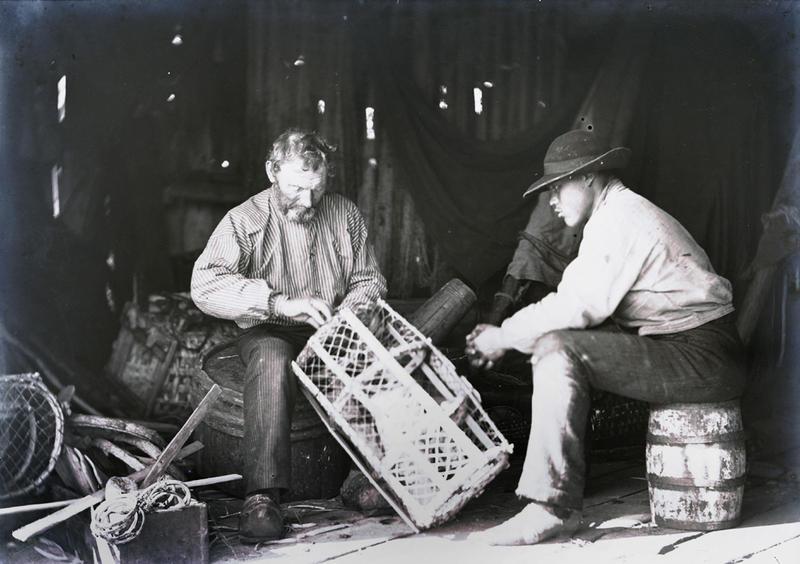 En eldre mann reparerer hummerteiner inne i et naust. Mannen er antagelig Lauritz Haalands far, Lars Haaland. Den unge mannen følger nøye med. Foto: Stavanger Sjøfartsmuseum, ST.S 1983-057-0213.