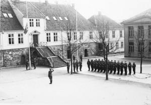 De tyske okkupasjonstroppene heiser flagg på Kongsgård skole, Stavanger 9. april 1940. Foto: Greve/ Stavanger maritime museum.