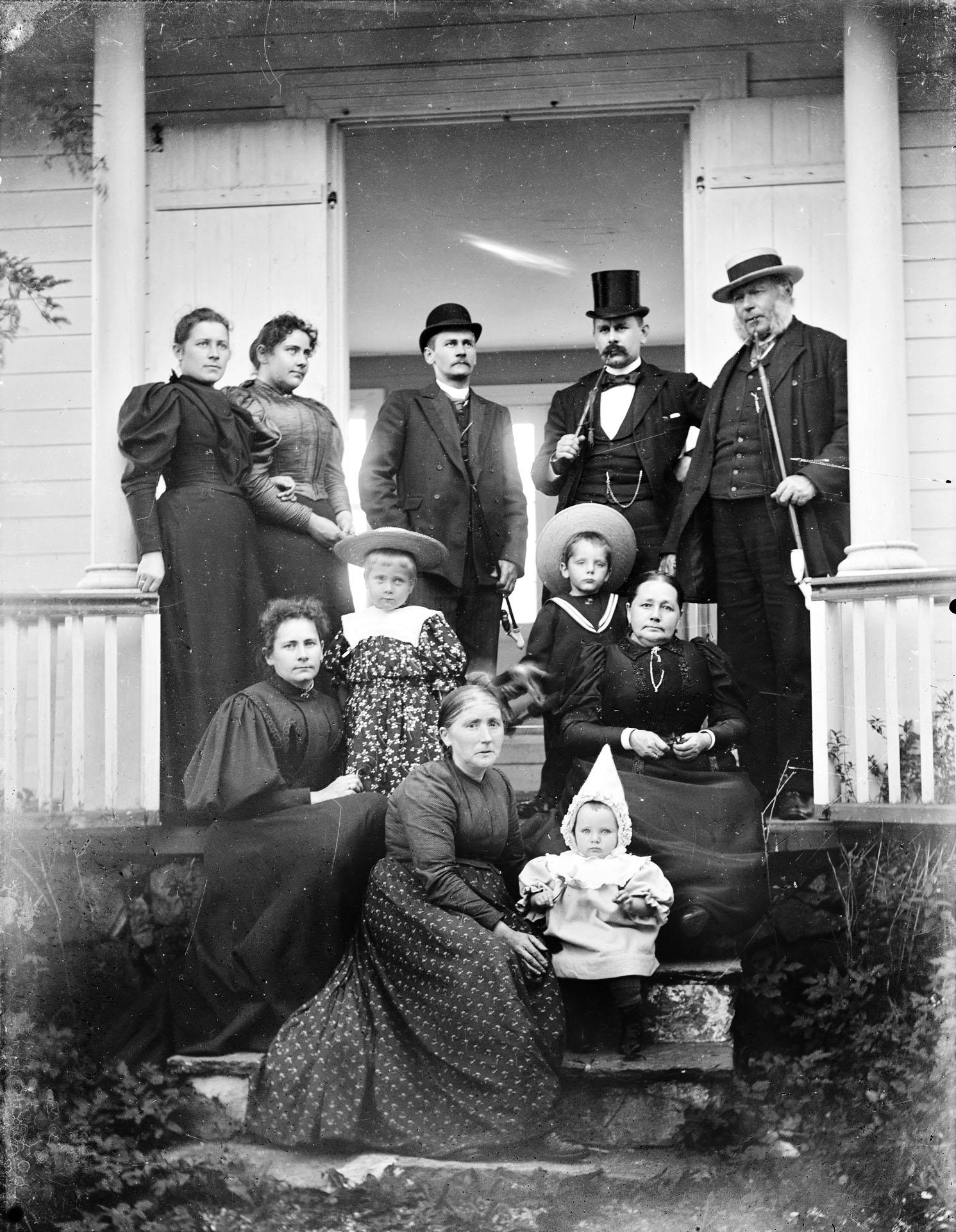 """Familien Bøe på landstedet på Slettebø i Egersund, foto tatt foran lysthuset. Antatt fotografert 1898. Fra venstre: Bakerst: Kirsten Bøe, Anna Bøe, Ole Hamre Bøe, Dr. Wilhelm Bøe, Wilhelm Bøe. Foran: Engel Hveding med datter Christine, sønn Wilhelm Hveding og Engel Bøe. Lengst framme: Barnepiken """"Goa"""" med Engel Hveding. Foto: E. H. Torjusen, DFF-EHT0063 (retusjert)."""
