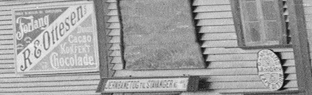 """Skilt på dampskipskaien i Egersund. Fra venstre ser vi reklame for """"R. E. Ottesens Chokolade"""", et skilt som forteller om """"Jernbanetog til Stavanger"""" og til slutt logoen til """"J. Hiorth Dampskibs Expedition"""". Ca. 1900. Foto: Erik Hadland Torjusen, DFF-EHT0304 (utsnitt)."""