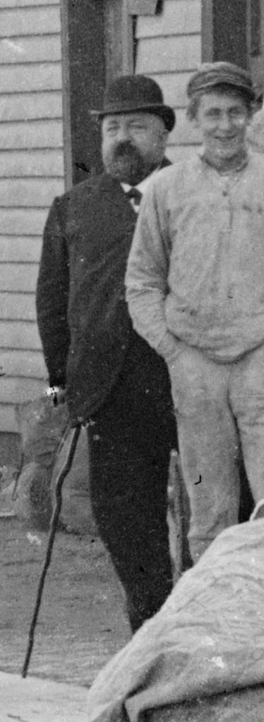 Til venstre ser vi innehaveren av dampskipsekspedisjonen, dampskipsekspeditør Jacob Fredrik de Rytter Hiorth. Mannen til høyre er ukjent. Cirka 1900. Foto: Erik Hadland Torjusen, DFF-EHT0304 (utsnitt).