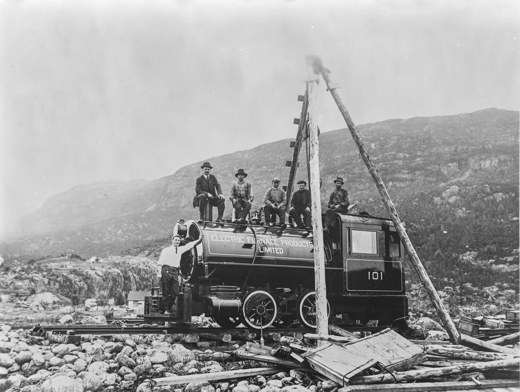 Stolte arbeidarar og funksjonærar på eit flunkande nytt lokomotiv med firmanamnet på.