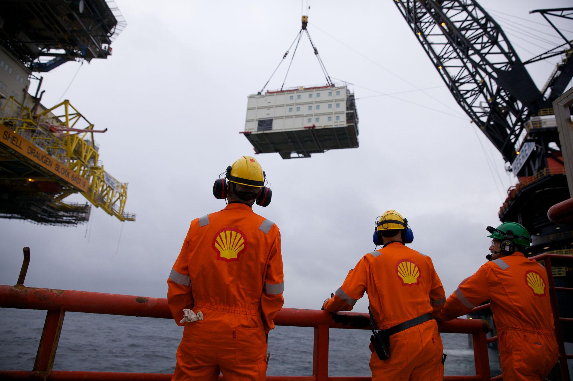 Shell-arbeidere står spent og overvåker det tunge løftet. Foto:Ukjent